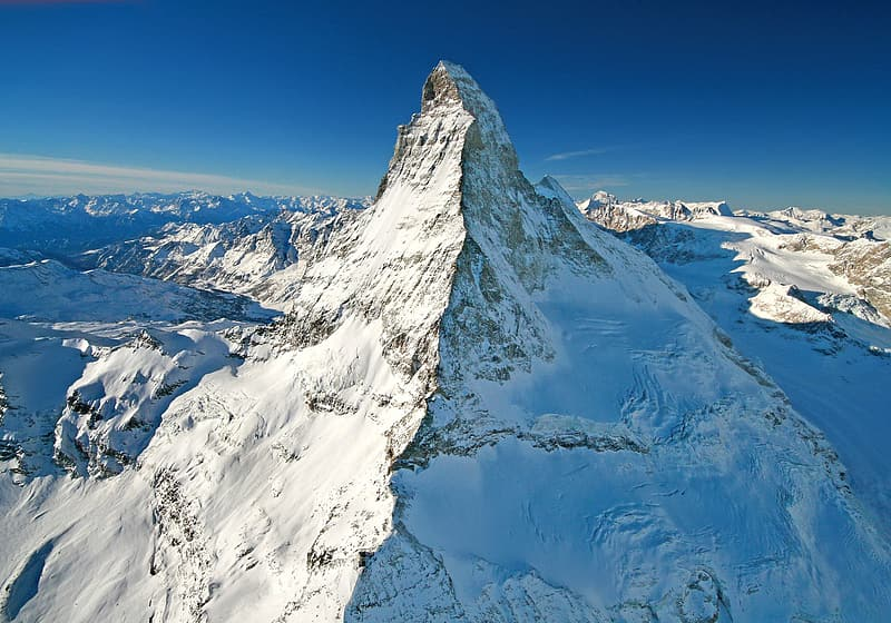 Mountain covered with white snow under blue sky aerial photography