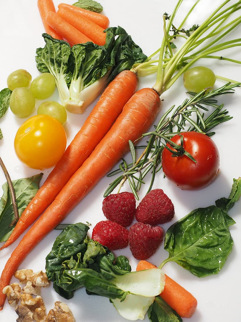 Carrots, strawberries, tomatoes, and cabbage arrange on white textile