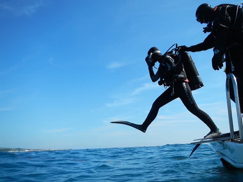 Person preparing to dive in body of water