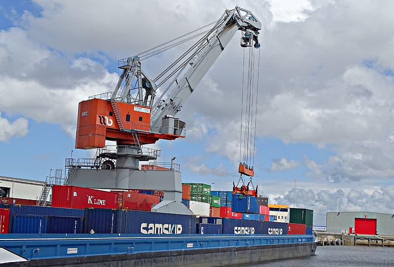 Blue and red intermodal container on ship during daytime