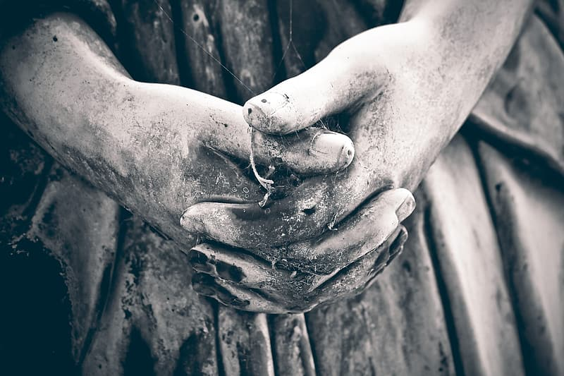 Grayscale photo of persons hand with water droplets