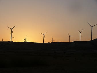 Silhouette of wind mills during golden hour