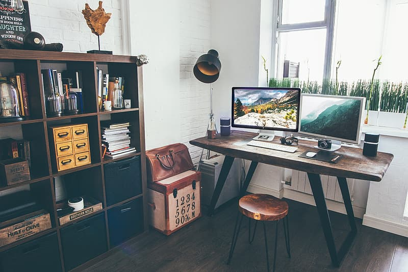 Two white flat screen computer monitors on brown wooden table