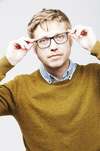 Close photo of man wearing black framed eyeglasses and green crew-neck knitted sweater