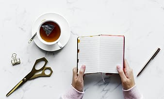 Person holding white book with black scissors and white ceramic mug with coffee