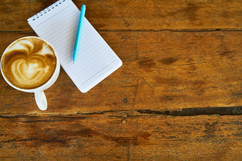 Cup of espresso beside ruled paper and ballpoint pen