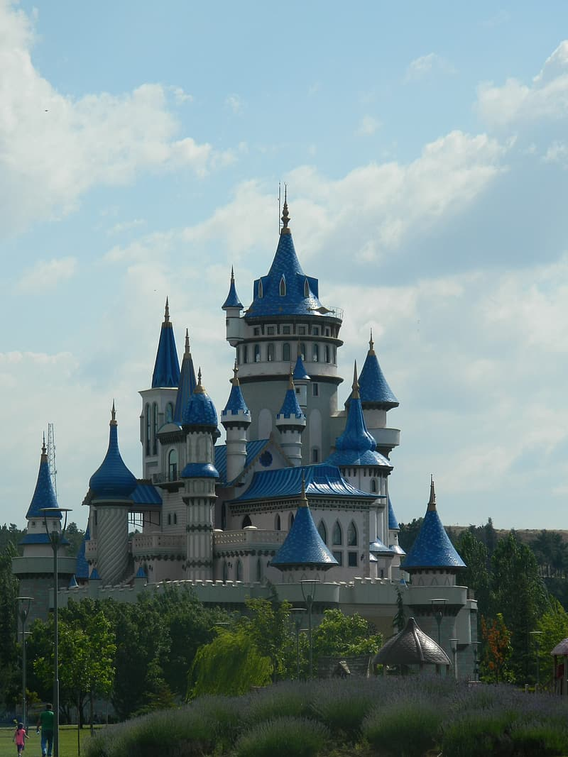 Blue and white castle under white clouds during daytime
