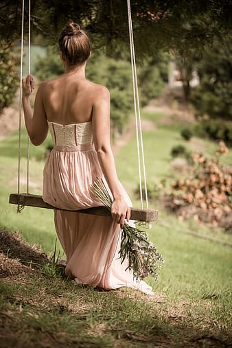 Woman wearing pink strapless dress sitting on brown sing during daytime
