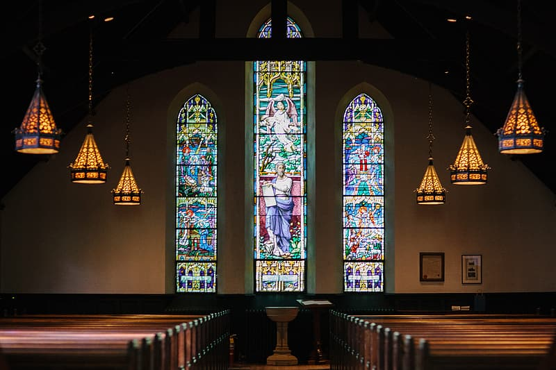 Church interior with blue green and yellow glass windows