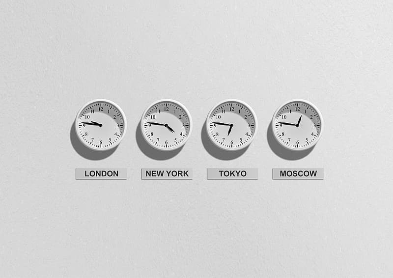 Four round white analog wall clocks