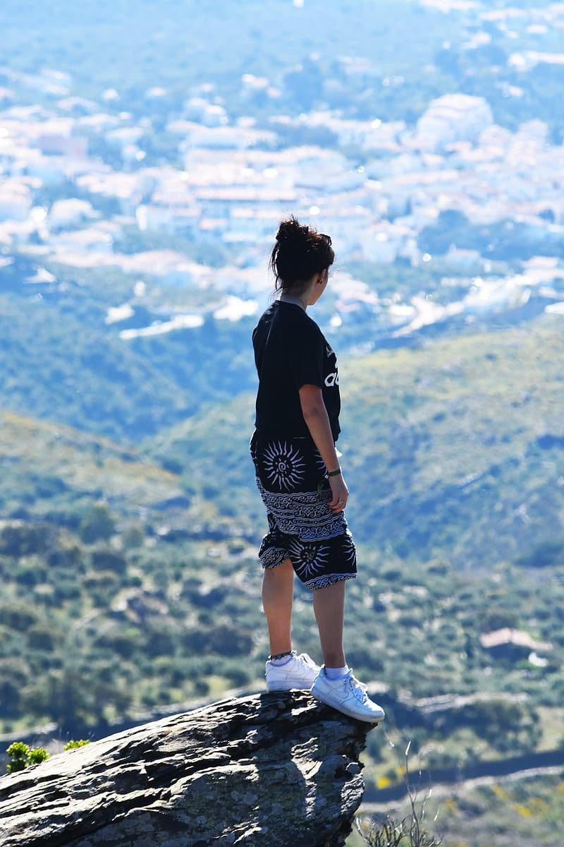 Black haired woman in black top and shorts on mountain cliff during day time