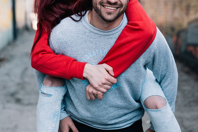 Man wearing grey sweater with woman wearing red sweater