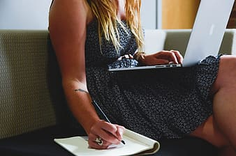 Woman writing notes and holding laptop computer