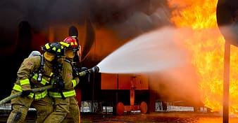 Two fireman holding fire hose with water splashes on flame