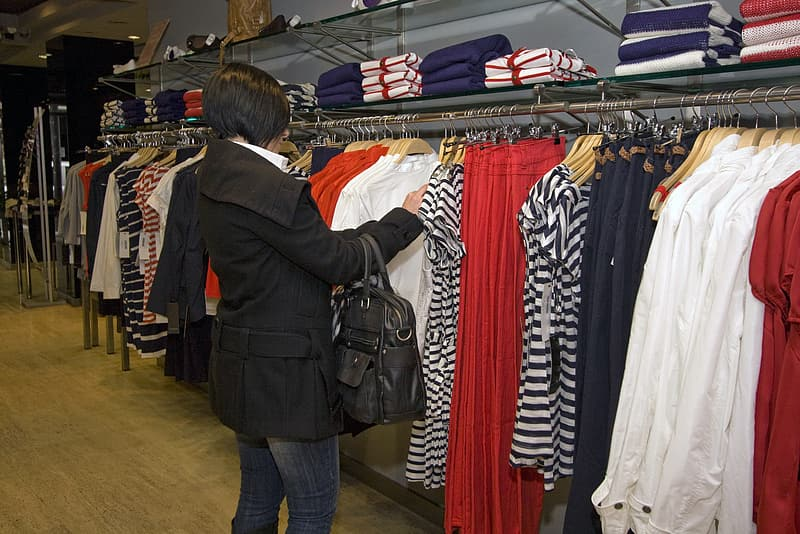 Woman looking on assorted-color clothes hanged on rack