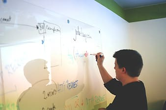 Man in black long sleeve shirt writing on white board