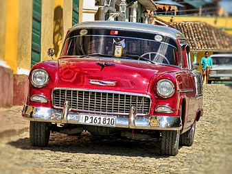 Red and white vintage car on road during daytime