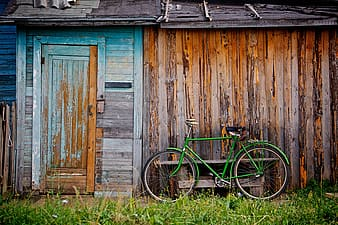 Photo of green bike near brown wooden house