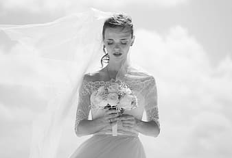 Grayscale photo of woman wearing wedding gown holding bouquet