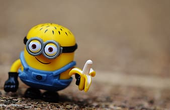 Close-up photography of Minion holding banana plastic toy
