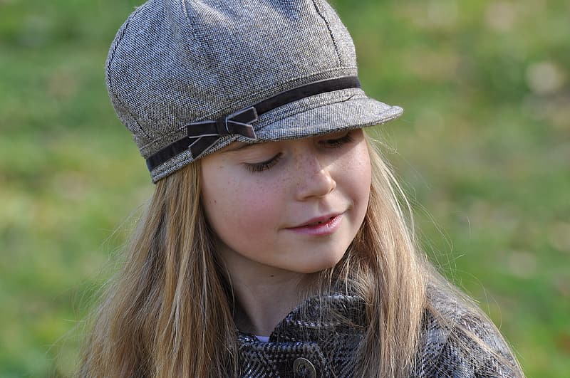 Close-up photography of girl wearing grey coat and grey cap during daytime