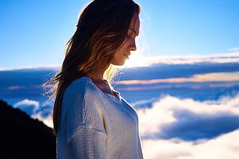 Woman in white top standing near clouds on top of mountain