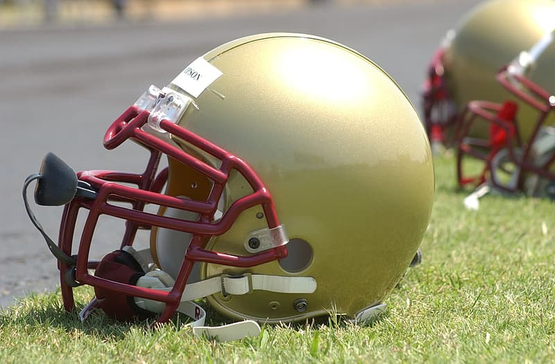 Green and red football helmet on green grass