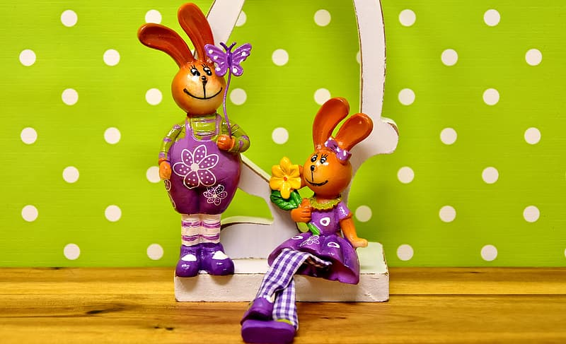 Two rabbit figurines wearing purple dresses