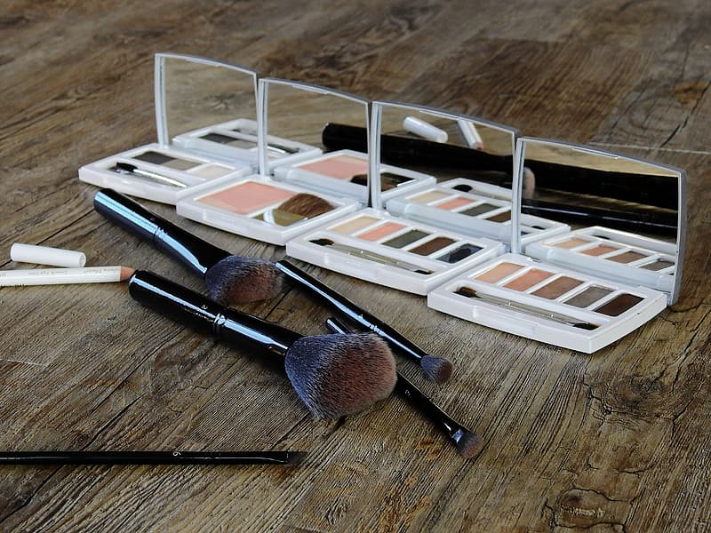 Photo of four makeup palettes beside brush set