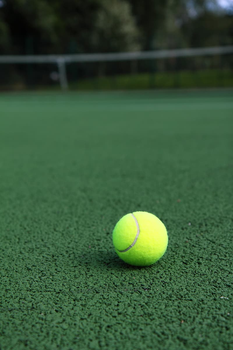 Selective focus photography of green tennis ball on sod at daytime