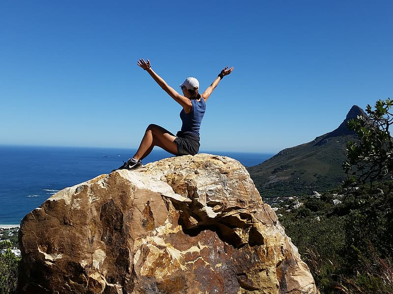 Woman wearing blue tank top sitting in top of rock with a view of sea