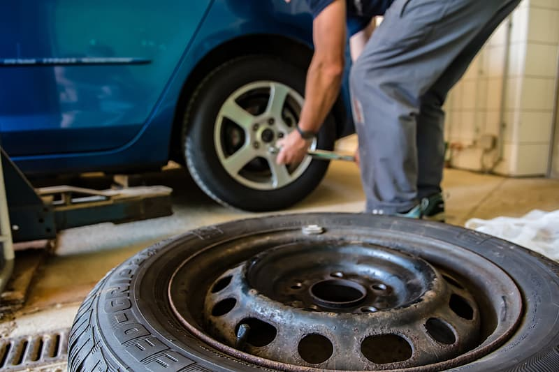 Close-up photo of person changing tire of a blue vehicle