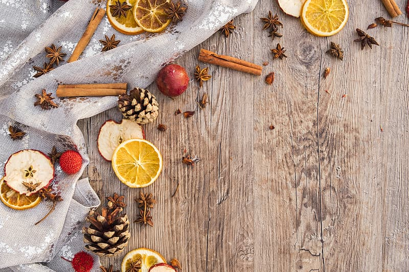 Sliced citrus fruits and cinnamon rolls on brown wooden surface