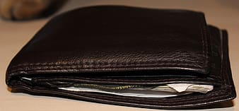 Brown leather bifold wallet on white surface