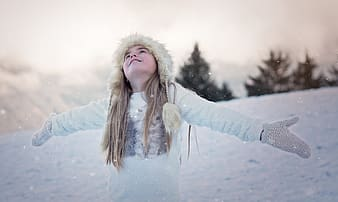 Girl wearing fur cap and white crew-neck long-sleeved shirt opening his arms to catch snow during daytime