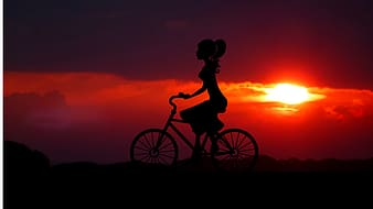 Silhouette of woman riding bicycle during sunset