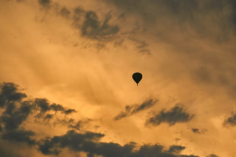 Silhouette of hot air balloon under cloudy sky during sunset