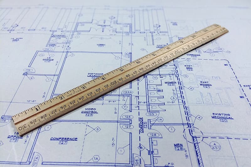 Brown wooden ruler on top of floor plan