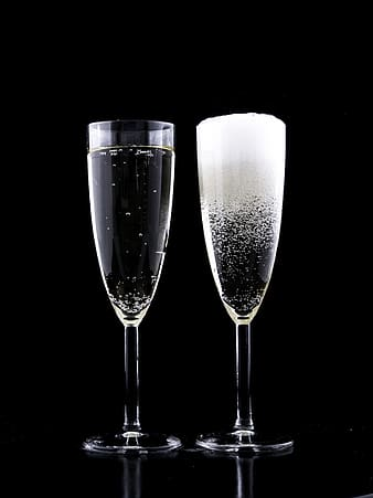 Two clear wineglasses filled with clear liquids