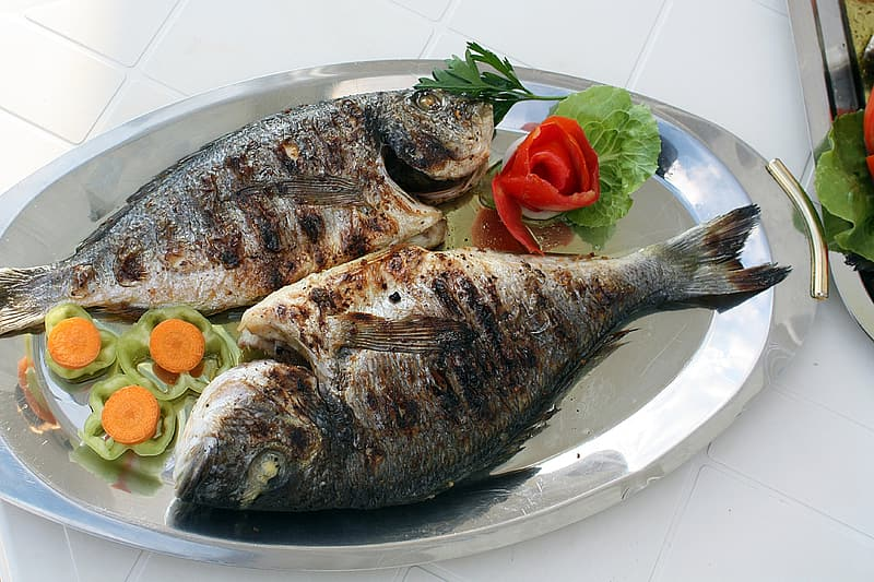 Two grilled fish with vegetables on gray stainless steel plate