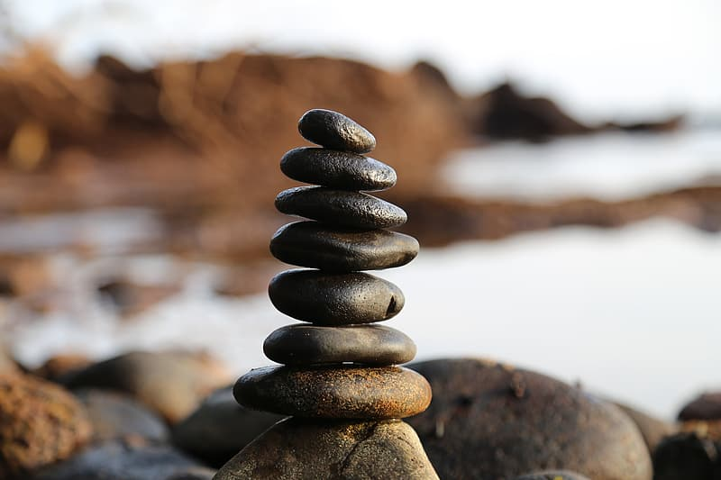 Selective focus photography of stones balanced on rock