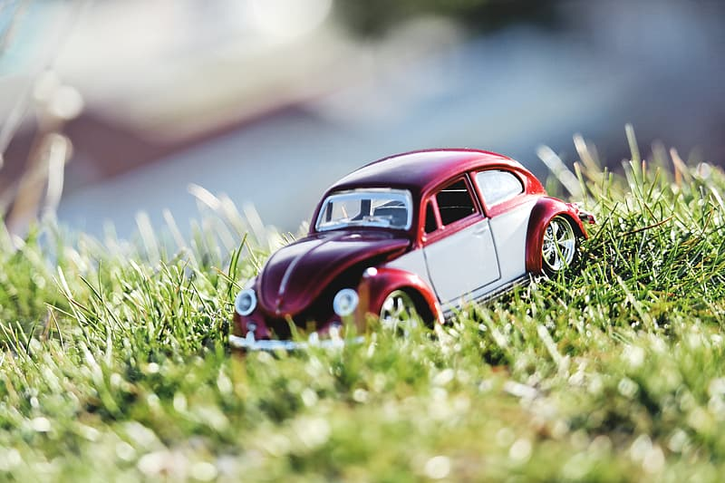 Red and white Volkswagen Beetle coupe scale model on grass at daytime