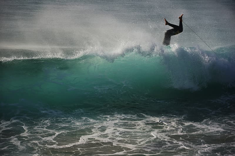 Photo of person falling on surfboard in body of water
