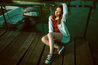 Woman wearing red shirt, gray cardigan, and pair of black low-top sneakers outfit sitting on brown wooden dock