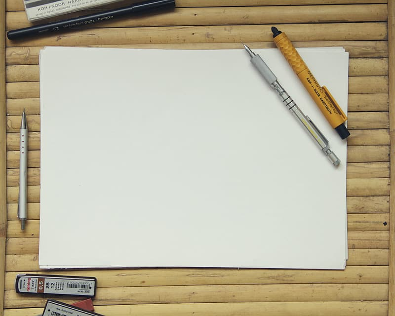 White paper beside pens and erasers on top of brown wooden surface