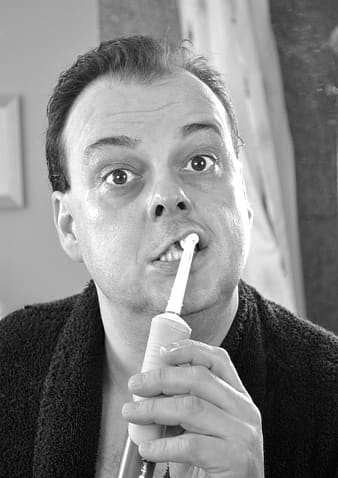 Man brushing his teeth in grayscale photography