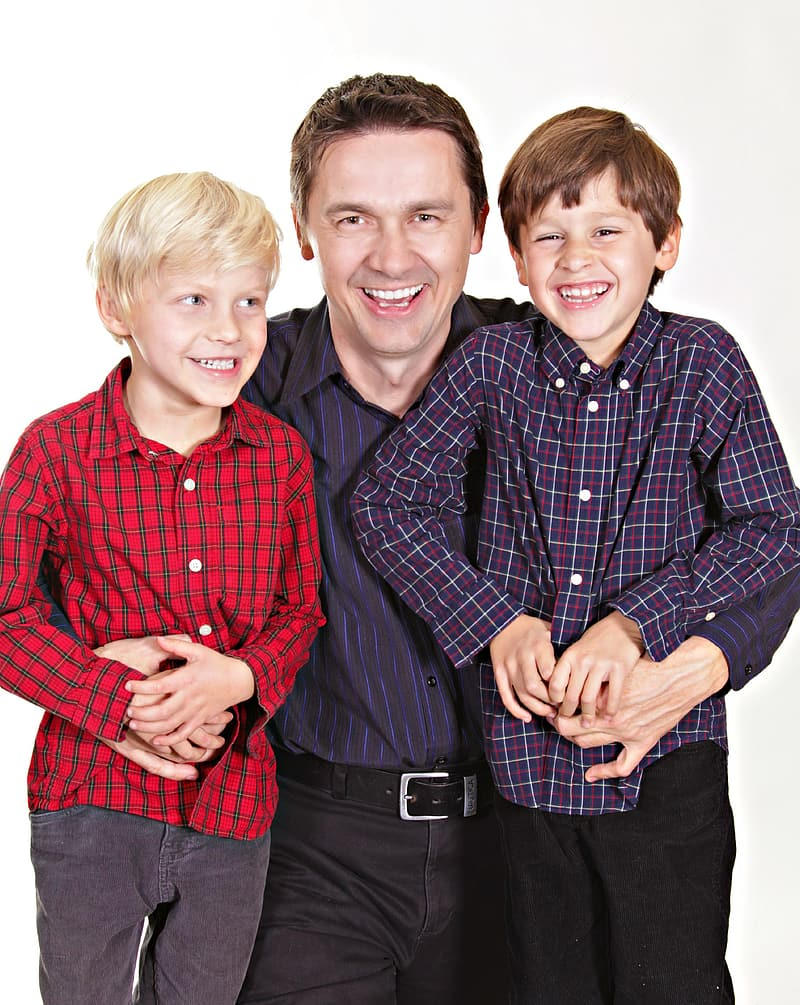 Man wearing black and purple dress shirt in between of two childs