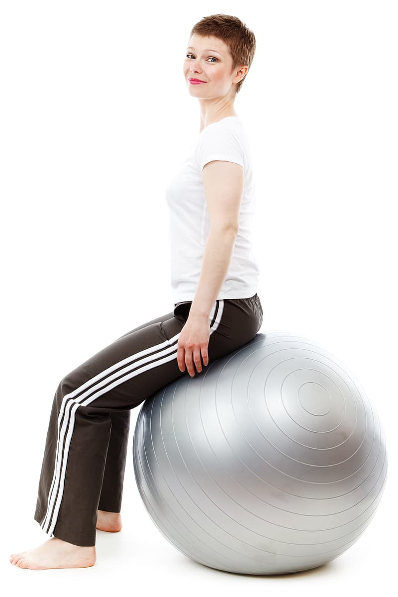 Woman in white shirt and black sweat pants sitting on gray stability ball