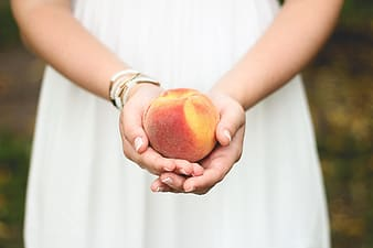 Woman in white dress holding peach