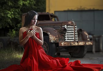 Woman in red dress near brown utility truck